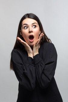 Frau im schwarzen pullover zeigt suprice
