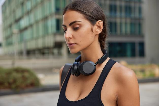 Frau im schwarzen t-shirt verwendet drahtlose kopfhörer beim training im freien konzentriert nach unten denkt über etwas nach, das in der innenstadt gegen unscharf steht