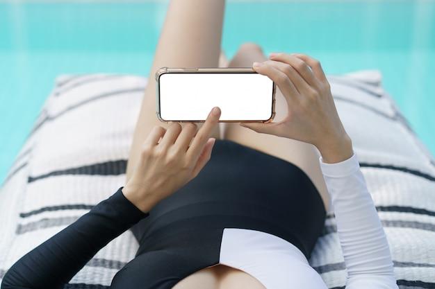 Frau im schwarzweiss-badeanzug, der leeres handy mit weißem bildschirm nahe pool hält.