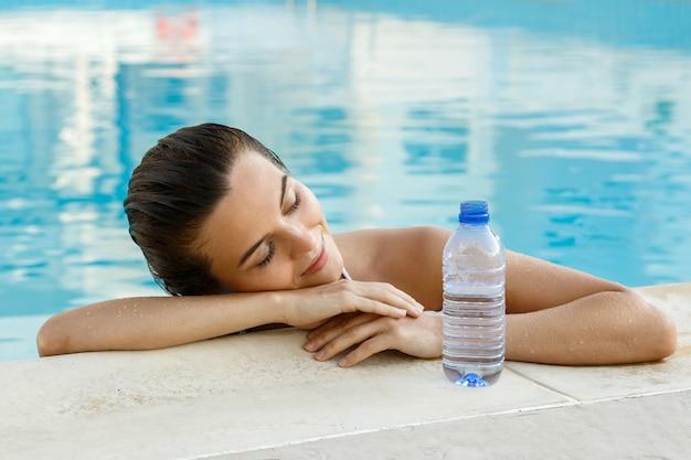 Frau im schwimmbad mit einer flasche wasser