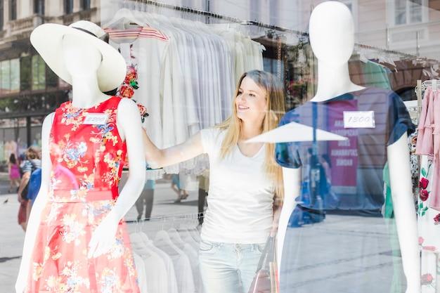 Frau im shop, der mannequin betrachtet