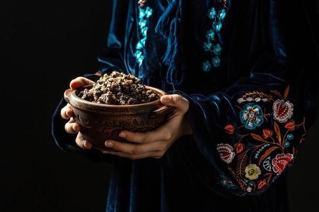 Frau im slawischen kleid, das schüssel mit traditioneller kutia hält