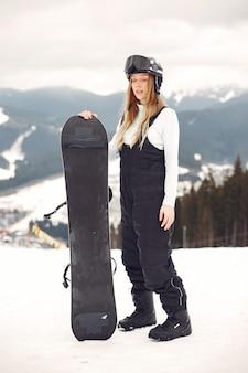 Frau im snowboardanzug. sportlerin auf einem berg mit einem snowboard in den händen am horizont. konzept zum sport