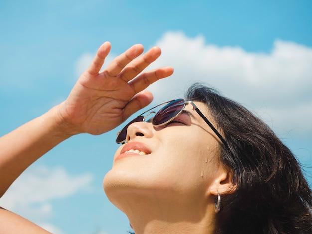Frau im sommer. lächelnde schöne asiatische frau mit kurzen haaren mit sonnenbrille und weißem ärmellosem hemd, die an einem sonnigen tag im sommer nach oben schaut und die augen mit ihrer hand auf blauem himmelshintergrund schattiert.