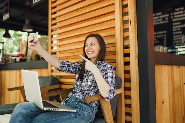 Frau im sommercafé aus holz im freien, das mit laptop-pc-computer sitzt, selfie-aufnahme auf dem handy macht und sich in der freizeit entspannt mobiles büro