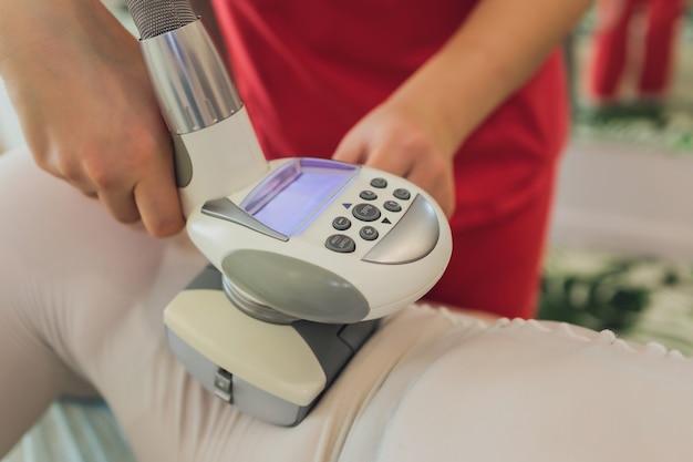 Frau im speziellen weißen anzug, der anti-cellulite-massage in einem spa-salon erhält.
