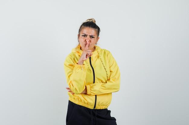 Frau im sportanzug, der stille geste zeigt und ernst, vorderansicht schaut.