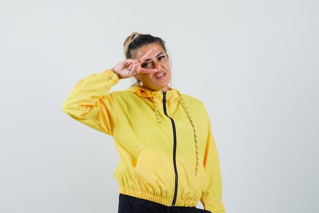 Frau im sportanzug zeigt siegeszeichen auf auge und schaut zuversichtlich, vorderansicht.