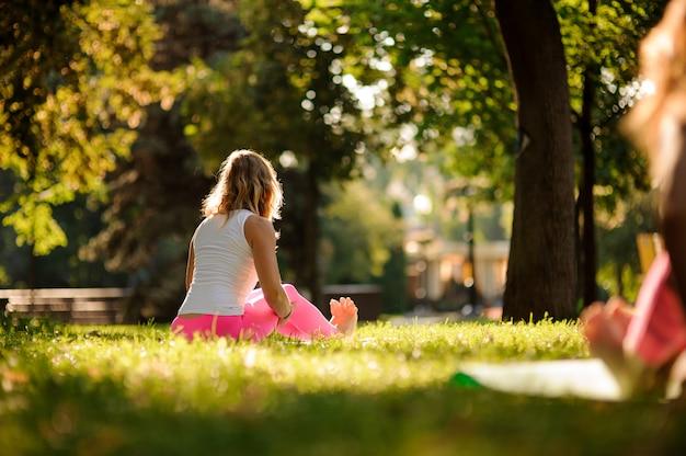 Frau im sportsuit, das unterschiedliches yoga übt, wirft im park auf