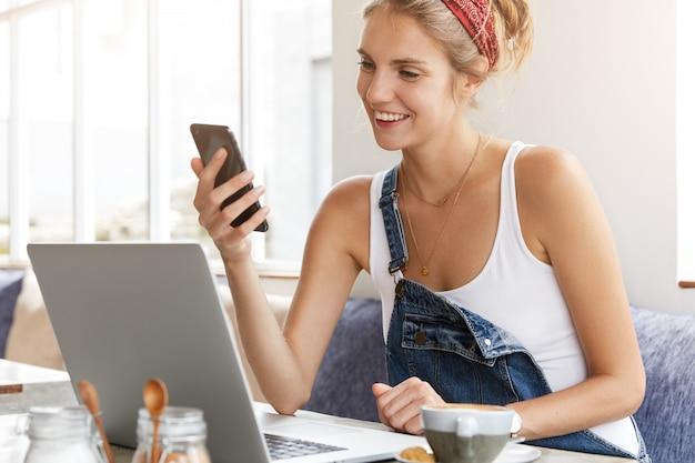 Frau im stilvollen jeansoverall mit laptop im coffeeshop