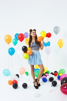 Frau im stilvollen outfit, das mit luftballons an der hellen partei aufwirft