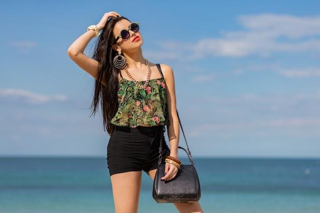 Frau im stilvollen tropischen autfit, das am strand aufwirft.