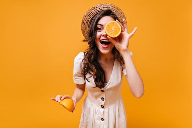 Frau im stilvollen weißen kleid und im strohhut lacht und hält orangenscheiben.