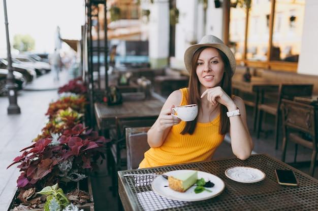 Frau im straßencafé im freien, die am tisch in gelbem kleiderhut mit einer tasse cappuccino, kuchen sitzt und sich in der freizeit im restaurant entspannt?