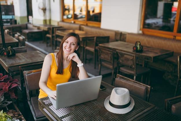 Frau im straßencafé im freien, die am tisch sitzt und an einem modernen laptop-pc arbeitet und sich in der freizeit im restaurant entspannt?