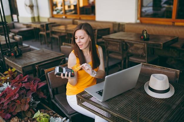 Frau im straßencafé im freien, die mit laptop-pc sitzt, hält drahtloses modernes bankzahlungsterminal, um kreditkartenzahlungen zu verarbeiten