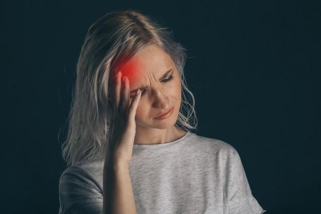 Frau im stress mit schmerzen im gesicht, die kopfschmerzen fühlen.