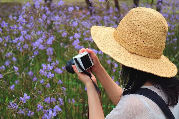 Frau im strohhut, die fotos des lila blumenfeldes macht
