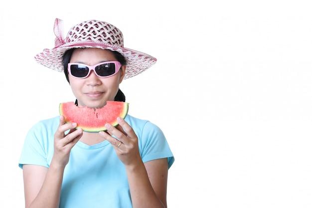Frau im strohhut halten eine scheibe wassermelone.