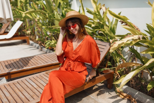Frau im strohhut und im orangefarbenen spielanzug, die während des urlaubs auf bali auf ihrer villa ruhen.
