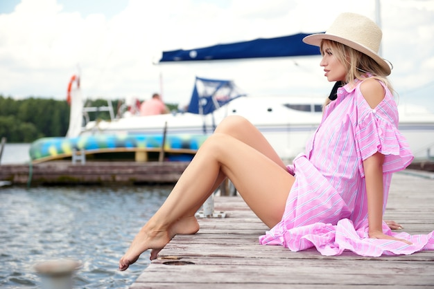 Frau im strohhut und im rosa kleid, die im sommer auf dem pier ruhen