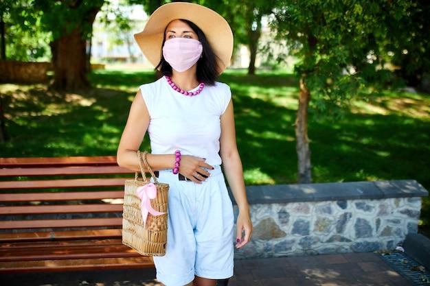 Frau im strohhut und in der tasche, die rosa schutzmaske trägt, im park im freien in der stadt, konzeptselbstpflege, leben während der coronavirus-pandemie, covid-19.