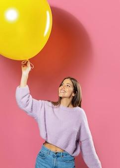 Frau im studio, die spaß mit luftballons hat