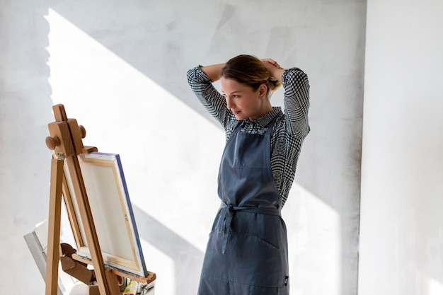 Frau im studio mit leinwand und staffelei