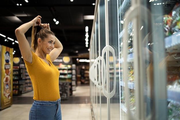 Frau im supermarkt, der lebensmittel im gefrierschrank wählt