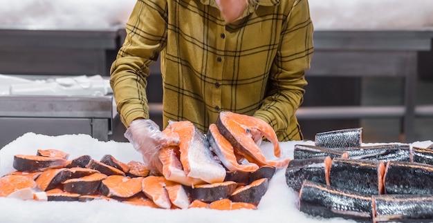 Frau im supermarkt. schöne junge frau, die einen lachsfisch in ihren händen hält.