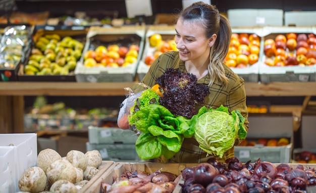 Frau im supermarkt. schöne junge frau, die in einem supermarkt einkauft und frisches bio-gemüse kauft