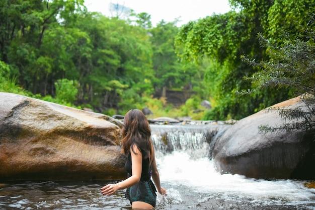 Frau im swimsuite am dschungel und am wasserfall