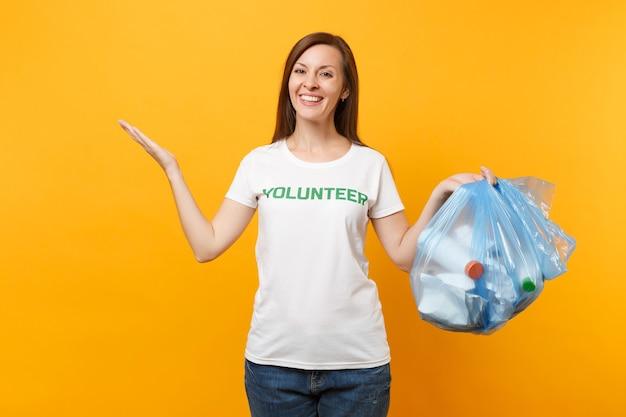 Frau im t-shirt freiwilliger, müllsack auf gelbem hintergrund isoliert. freiwillige kostenlose hilfshilfe, nächstenliebe. problem der umweltverschmutzung. stoppen sie das konzept des naturmüll-umweltschutzes.