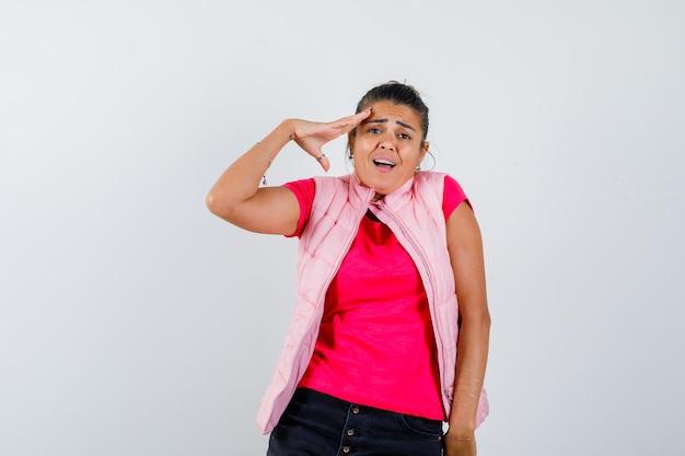 Frau im t-shirt, weste, die grußgeste zeigt und verängstigt aussieht