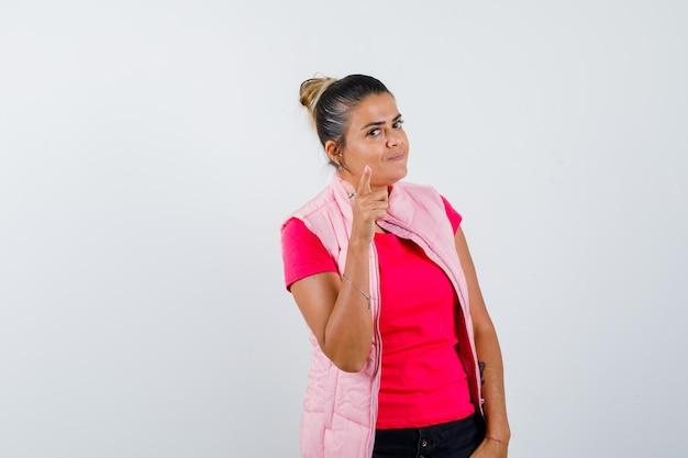 Frau im t-shirt, weste, die mit dem finger auf die kamera zeigt und selbstbewusst aussieht