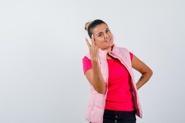 Frau im t-shirt, weste, die siegesgeste zeigt und selbstbewusst aussieht