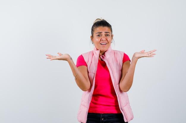 Frau im t-shirt, weste, die skalengeste macht und selbstbewusst aussieht