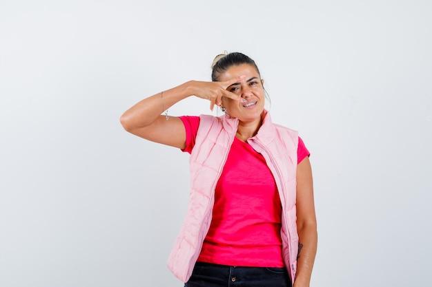Frau im t-shirt, weste mit v-zeichen auf dem auge und selbstbewusst aussehend