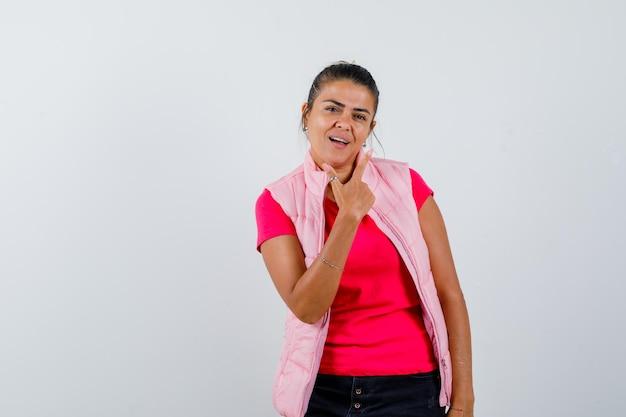 Frau im t-shirt, weste zeigt mit dem finger nach oben und sieht selbstbewusst aus looking
