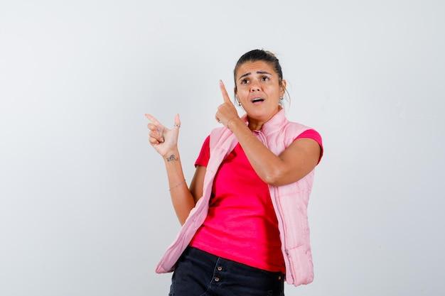 Frau im t-shirt, weste zeigt mit dem finger nach oben und sieht verwirrt aus