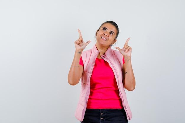 Frau im t-shirt, weste zeigt nach oben und sieht fröhlich aus