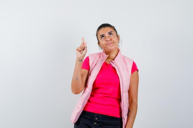 Frau im t-shirt, weste zeigt nach oben und sieht zögerlich aus