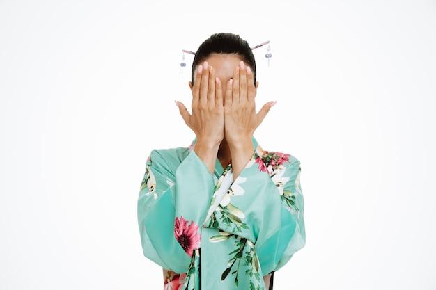 Frau im traditionellen japanischen kimono, der das gesicht mit den armen auf weiß kegelt