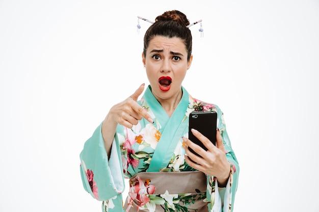 Frau im traditionellen japanischen kimono, der smartphone hält und mit zeigefinger darauf zeigt, besorgt und verwirrt auf weiß
