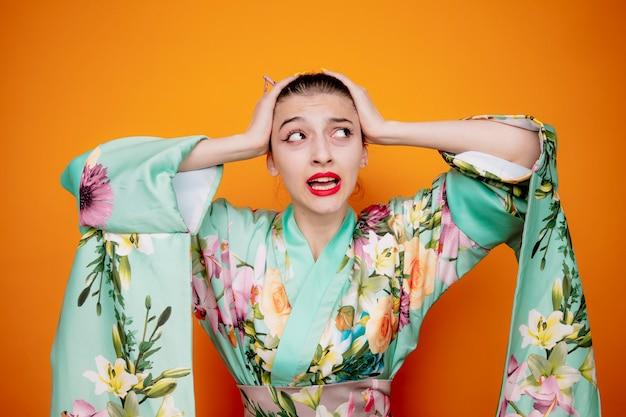 Frau im traditionellen japanischen kimono, die besorgt und verwirrt aufschaut und die hände auf dem kopf hält, weil sie auf orange irrt