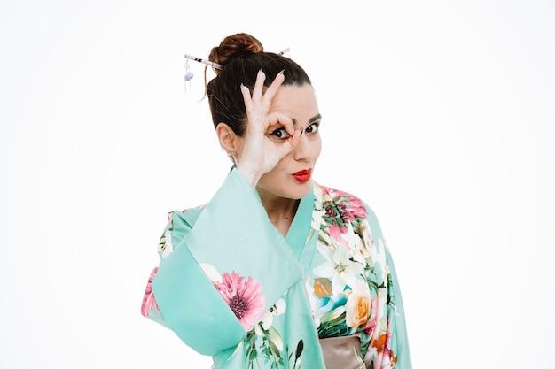 Frau im traditionellen japanischen kimono, die ein gutes zeichen tut, das durch die finger glücklich und fröhlich auf weiß schaut