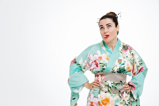 Frau im traditionellen japanischen kimono, die glücklich und fröhlich aufschaut und die zunge auf weiß herausstreckt