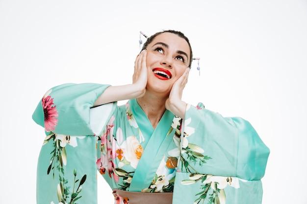 Frau im traditionellen japanischen kimono, die glücklich und überrascht aufschaut und träumt, die hände auf ihren wangen hält und breit auf weiß lächelt