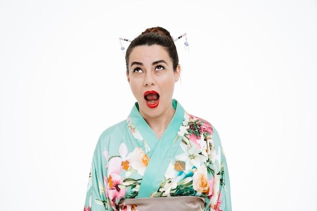 Frau im traditionellen japanischen kimono, die irritiert und genervt auf weiß aufschaut