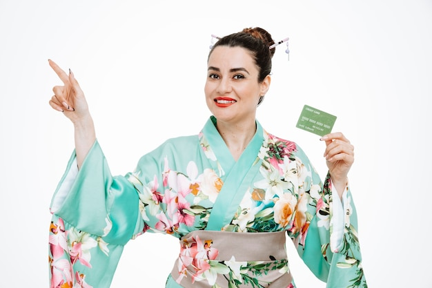 Frau im traditionellen japanischen kimono, die kreditkarte hält, die mit dem zeigefinger zur seite auf weiß zeigt Kostenlose Fotos